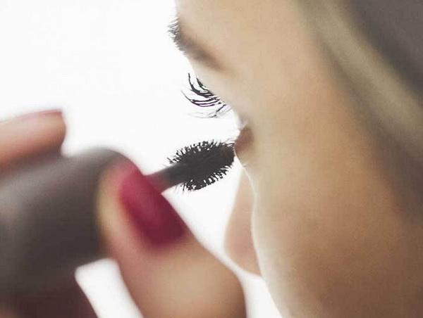 Девушка красит ресницы