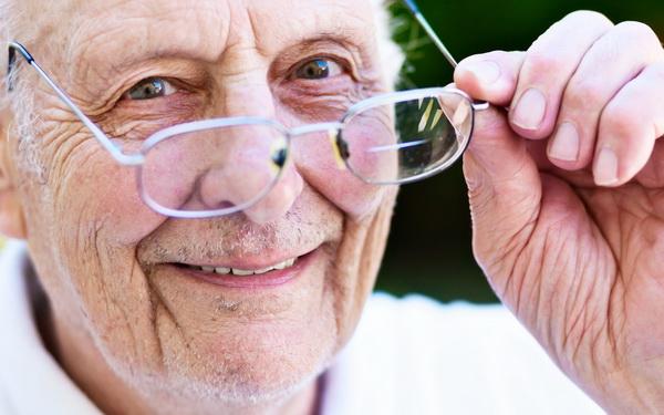 Мужчина снимает очки